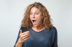 Geschokte jonge vrouw die bij mobiel haar staren Royalty-vrije Stock Afbeelding