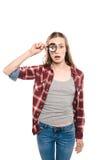Geschokte jonge vrouw die meer magnifier throungh kijken Stock Foto