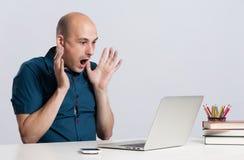 Geschokte kale mens die laptop bekijken stock fotografie