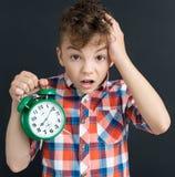 Geschokte leerling met grote groene wekker - terug naar school concep royalty-vrije stock afbeeldingen
