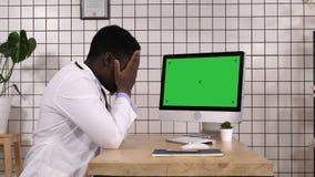 Geschokte medische arts die op het scherm van computer kijken Witte vertoning