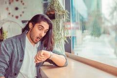 Geschokte mens die aan polshorloge voor tijd kijken, die laat zijn stock foto