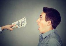 Geschokte mens die de rekeningen van de contant gelddollar bekijken Royalty-vrije Stock Foto