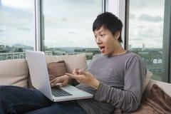 Geschokte mens die laptop op bank thuis met behulp van Royalty-vrije Stock Foto's