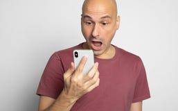 Geschokte mens die zijn smartphone bekijken stock fotografie