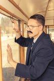 Geschokte mens met een snor in een kostuum met glazen die in stellen royalty-vrije stock fotografie