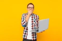 Geschokte mens met laptop, op gele achtergrond, mens die online winkelen stock afbeelding