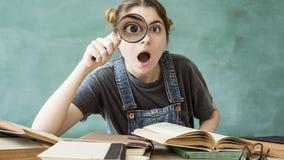 Geschokte student die door een vergrootglas kijken royalty-vrije stock foto