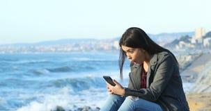 Geschokte tiener die goed online nieuws op het strand lezen stock footage