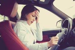 Geschokte vrouw in auto met documenten stock afbeelding