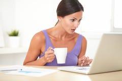 Geschokte vrouw die het Web op haar laptop doorbladeren Royalty-vrije Stock Foto