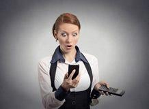 Geschokte vrouw die op de slimme calculator van de telefoonholding kijken stock afbeeldingen