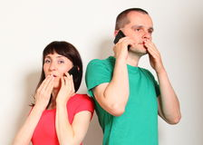 Geschokte vrouw en man die op mobiele telefoon spreken Stock Foto