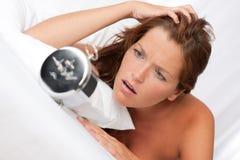Geschokte vrouw het letten op wekker Stock Foto's