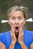 Geschokte Vrouw met weefsels als oordopjes voor lawaaibescherming Stock Afbeeldingen