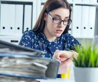 Geschokte vrouwelijke manager die haar horloge dichtbij een stapel van documenten bekijken Uiterste termijnconcept royalty-vrije stock foto's