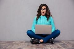 Geschokte vrouwenzitting op de vloer met laptop Stock Fotografie