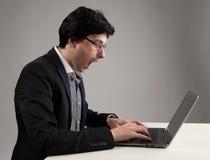 Geschokte zakenman die bij zijn laptop staren stock foto's