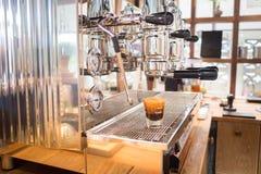 Geschossen vom Espresso in der Schale auf Kaffeemaschine Stockfotos
