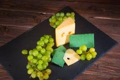 Geschossen vom Käse und von den grünen Trauben auf schwarzem Schiefer cheeseboard auf Holztisch Stockfotografie