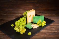 Geschossen vom Käse und von den grünen Trauben auf schwarzem Schiefer cheeseboard auf Holztisch Stockbilder