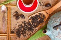 Geschossen vom trockenen schwarzen Tee mit Blumen Stockbild
