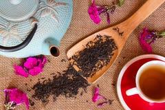 Geschossen vom trockenen schwarzen Tee mit Blumen Stockfotografie