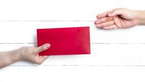 Geschossen von der Übergabe von roten Paketen für Geschenke des Chinesischen Neujahrsfests Lizenzfreie Stockfotos