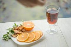 Geschossen von der Glastasse tee mit Orange auf hölzerner Tabelle Stockfotografie