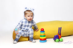 Geschossen von einem kleinen Baby, das mit einigen Spielwaren spielt und eine sippy Schale hält Stockfoto