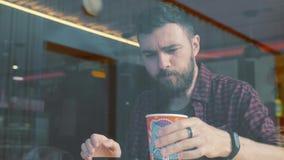 Geschossen von einem Mann, der im Café mit einem Smartphone sitzt Geschossen durch Caféshowfenster stock footage