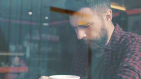 Geschossen von einem Mann, der im Café mit einem Smartphone sitzt Geschossen durch Caféshowfenster stock video footage