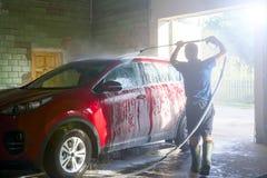 Geschossen von einem Mann, der sein Auto unter Hochdruckwasser wäscht Waschendes rotes Auto mit Seife Auto-Reinigung stockfoto
