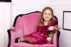 Geschossen von einem sch?nen kleinen M?dchen in einem Kleid mit einer Rose in ihren H?nden, welche die Kamera mit einem reizend L lizenzfreies stockbild