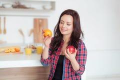 Geschossen von einer dunkelhaarigen kaukasischen Frau, die Äpfel mit Orangen vergleicht Lizenzfreie Stockfotografie