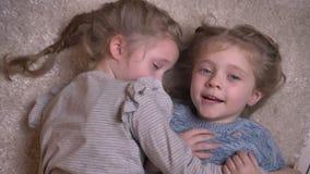 Geschossenes Spitzenporträt von zwei kleinen lustigen Mädchen, die froh auf dem Boden umarmen und küssen mit einander und liegen stock video footage