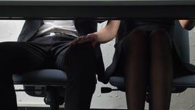 Geschoten in het kader van de lijst, raakt een jong chef- meisje zijn werknemers` s voet, hij tegenover, flirts, kwellingsconcept stock video