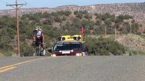 Geschoten van een concurrerende fietser op RAAM met zijn team erachter recht stock footage