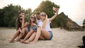 Geschoten van een groep jonge vrienden die een selfie op het strand nemen Mannen en vrouwen die foto's nemen die op een zand op w stock video