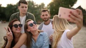 Geschoten van een groep jonge vrienden die een selfie op het strand nemen Mannen en vrouwen die foto's nemen die op een zand op w stock footage