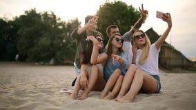 Geschoten van een groep jonge vrienden die een selfie op het strand nemen Mannen en vrouwen die foto's nemen die op een zand op w stock videobeelden