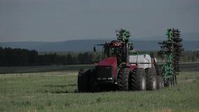 Geschoten van een tractor die binnen op een gebied werken, die het gras samenpersen stock video