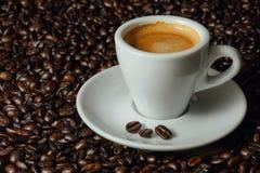 Geschoten van espresso op koffiebonen Stock Afbeeldingen