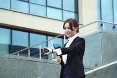 Geschoten van gelukkige smilling bedrijfsvrouw die de klok, het letten op tijd bekijken Royalty-vrije Stock Foto