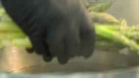 Geschoten van het koken van groene asperge in kokend water stock video