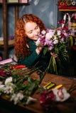 Geschoten van Kaukasische vrouwelijke zitting bij de lijst en ademhaling in aroma van bloemen royalty-vrije stock foto's