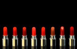 Geschoten van rode lippenstiften van verschillende kleur Op zwarte achtergrond Schoonheidsmiddelenconcept Mooie Luxe Moderne Hoog stock afbeelding