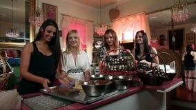 Geschoten van vier vrouwen die snoepjes in een boutique maken stock footage