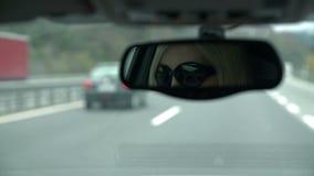 Geschoten van vrouw met zonnebril zichtbaar in achteruitkijkspiegel het drijven naar tunnel stock video