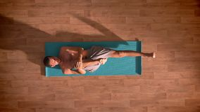 Geschotene de bovenkant, de Kaukasische mens liggen op een yogamat en rekken zijn die benen met ogen uit op de houten vloer worde stock footage